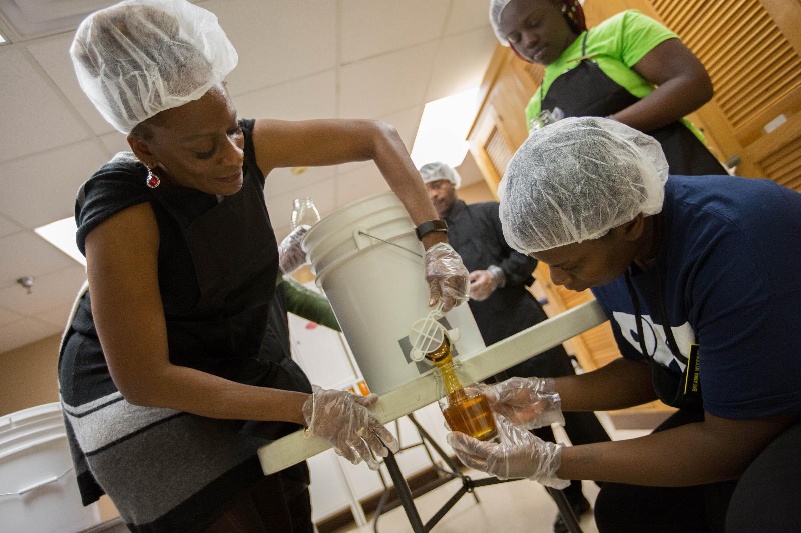 Commissioner Hill packaging honey with PKZ students